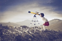 14068113 - little girl looking into a telescope on a hill